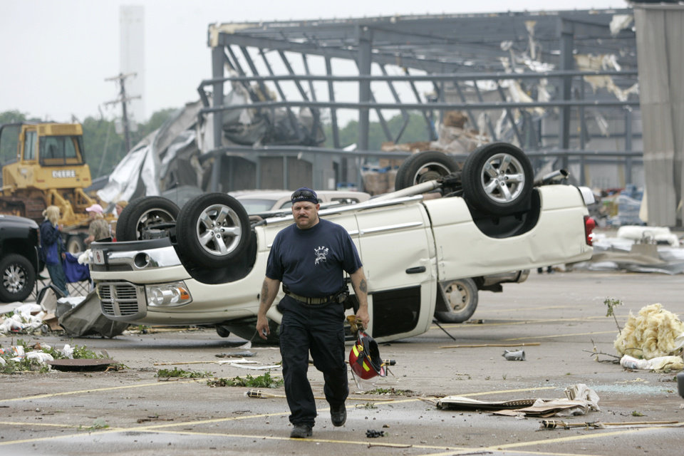 Photo - TORNADO / STORM DAMAGE: Little Axe Fire Department Captain David Spector walks across the Country Boy grocery store parking lot  in Little Axe, Oklahoma May 11 , 2010. Photo by Steve Gooch, The Oklahoman ORG XMIT: KOD