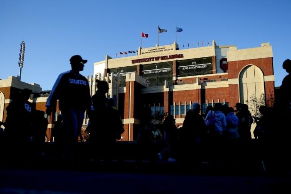 Photo -  Fans walk past Gaylord Family-Oklahoma Memorial Stadium before OU's game against Iowa State last season. [Bryan Terry/The Oklahoman]