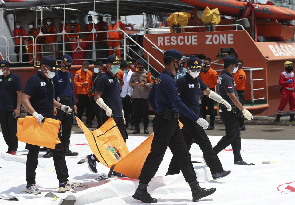 Photo -  CORRECTS TO THAT INVESTIGATORS CARRY PART OF A BODY - Investigators carry a part of a body recovered from the waters where Sriwijaya Air passenger jet crashed, at Tanjung Priok Port in Jakarta, Indonesia, Monday, Jan. 11, 2021. The search for the black boxes of a crashed Sriwijaya Air jet has intensified to boost the investigation into what caused the plane carrying dozens of people to nosedive into Indonesia seas. The Boeing 737-500 jet disappeared during heavy rain on Saturday. (AP Photo/Achmad Ibrahim)