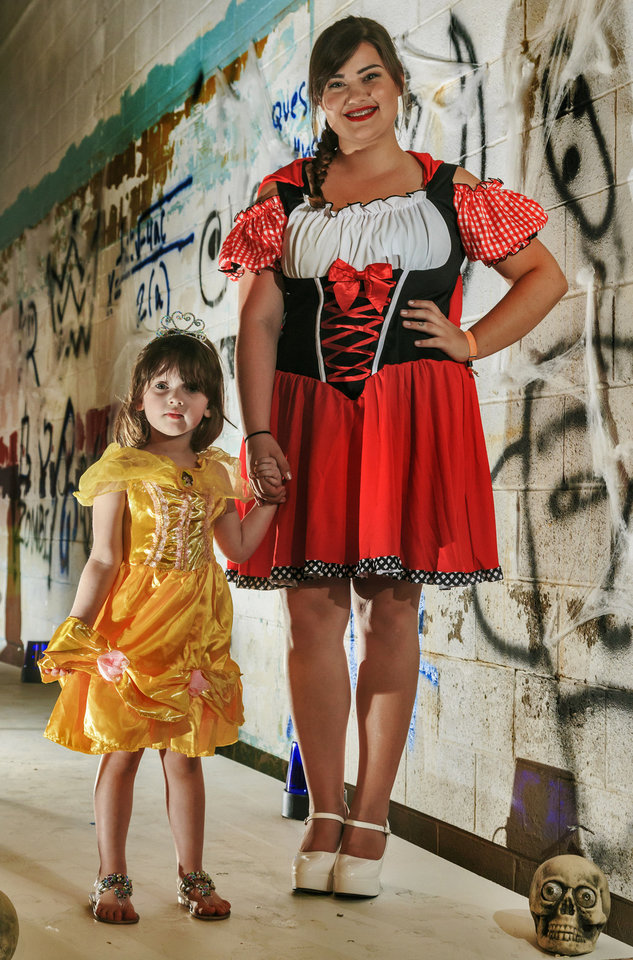 Photo - Stevie and Amber are sure to have a magical evening while trick or treating this Halloween.  Little Stevie is all beauty in this Belle  costume, available in adult and children's sizes.  Big sister Amber is ravishing as Little Red Riding Hood, with a detailed costume available in adult and plus sizes. Costumes sold at Party Galaxy. Photo by Chris Landsberger, The Oklahoman  CHRIS LANDSBERGER