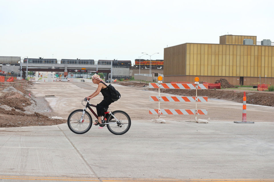 Photo -  A woman rides a bike north on Robinson where the Oklahoma City Boulevard will intersect. The OGE Energy Corp. data center, the gold colored building in the background, will be turned over to the city in early 2019 and will be cleared to make way for a 17-story Omni Hotel, a garage and eight-story Boulevard Place. [Photo by Doug Hoke, The Oklahoman]