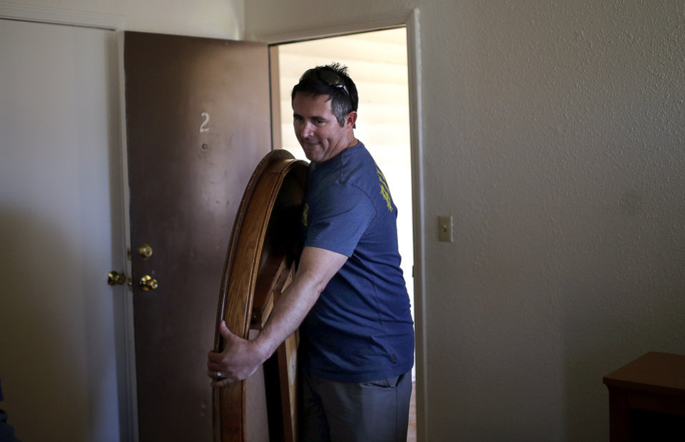 Photo -  Cam Sanders moves a dining table into Talisa Doonkeen's apartment, on May 1 in Oklahoma City. The group Focus on Home furnished the apartment for the single mother of two. Photo by Sarah Phipps, The Oklahoman   Sarah PhIpps -  Sarah Phipps