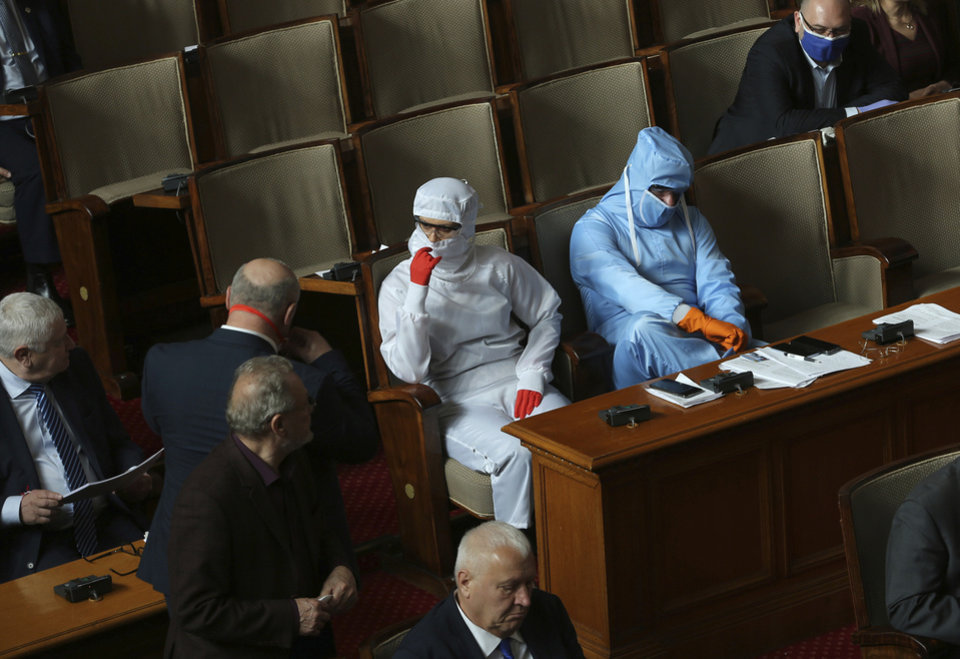 Photo -  Vesselin Mareshki, right, leader of Bulgarian Political party Volya, and an MP from from his party wear protective suits during Parliamentary session in the Bulgarian National Assembly in Sofia, Bulgaria, on Friday March 20, 2020. For some people the COVID-19 coronavirus causes mild or moderate symptoms, but for some it can cause very severe illness.(AP Photo/Vesselin Borishev)