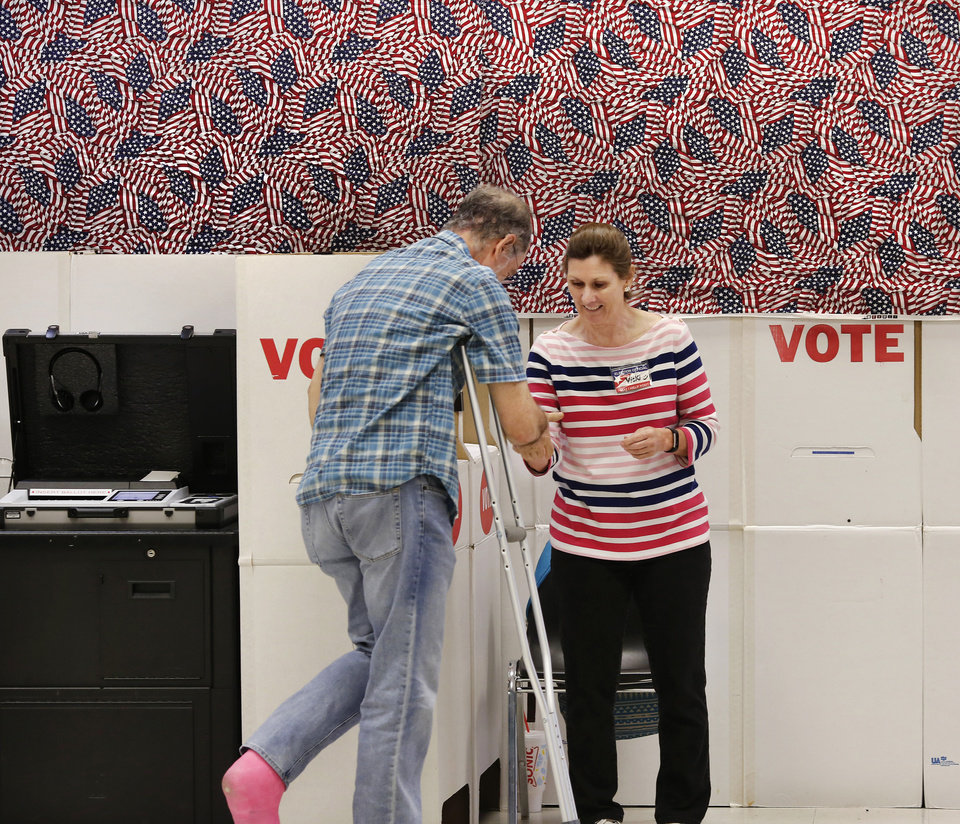 Photo -  Polling site worker Vicki Harris, right, gives an