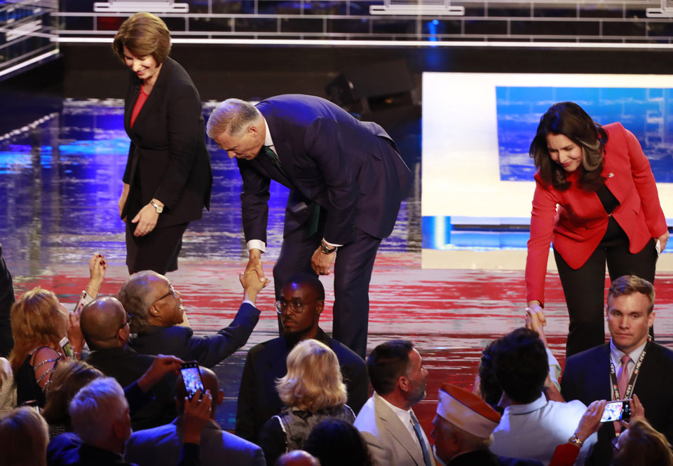 Photo - Democratic presidential candidates Sen. Amy Klobuchar, D-Minn., left, Washington Gov. Jay Inslee and Rep. Tulsi Gabbard, D-Hawaii, greet supporters at the end of a Democratic primary debate hosted by NBC News at the Adrienne Arsht Center for the Performing Arts, Thursday, June 27, 2019, in Miami. (AP Photo/Wilfredo Lee)
