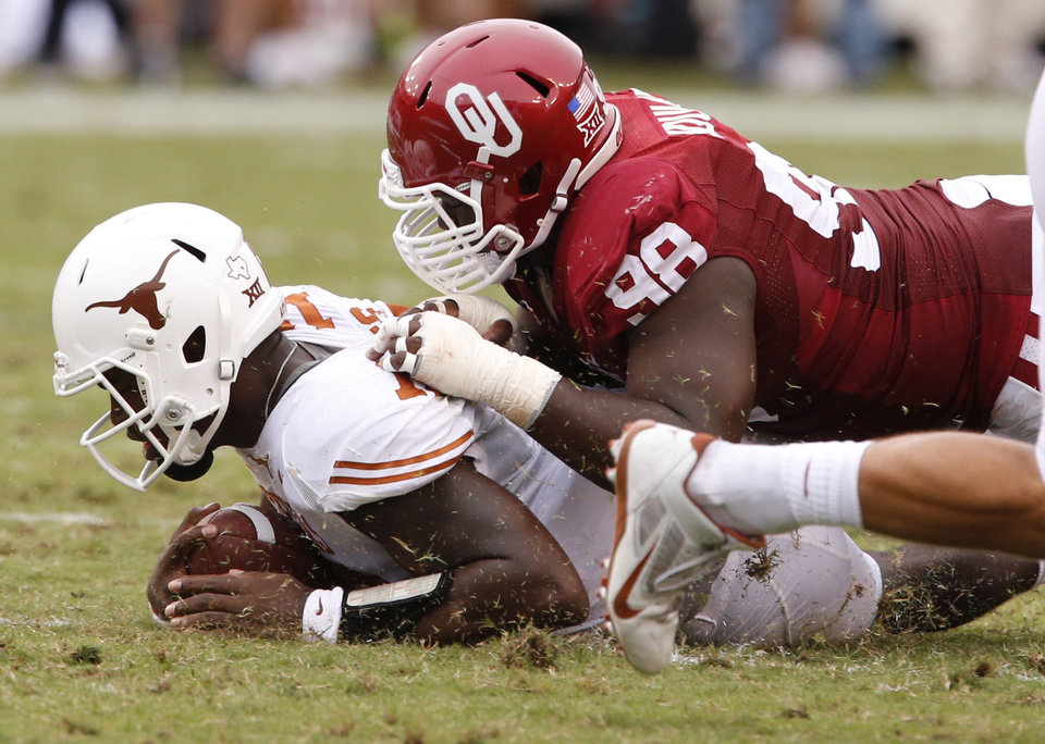 Photo - Oklahoma's Chuka Ndulue (98) stops Texas' Tyrone Swoopes (18) during the Red River Showdown college football game between the University of Oklahoma Sooners (OU) and the University of Texas Longhorns (UT) at the Cotton Bowl in Dallas, Texas on Saturday, Oct. 11, 2014. 