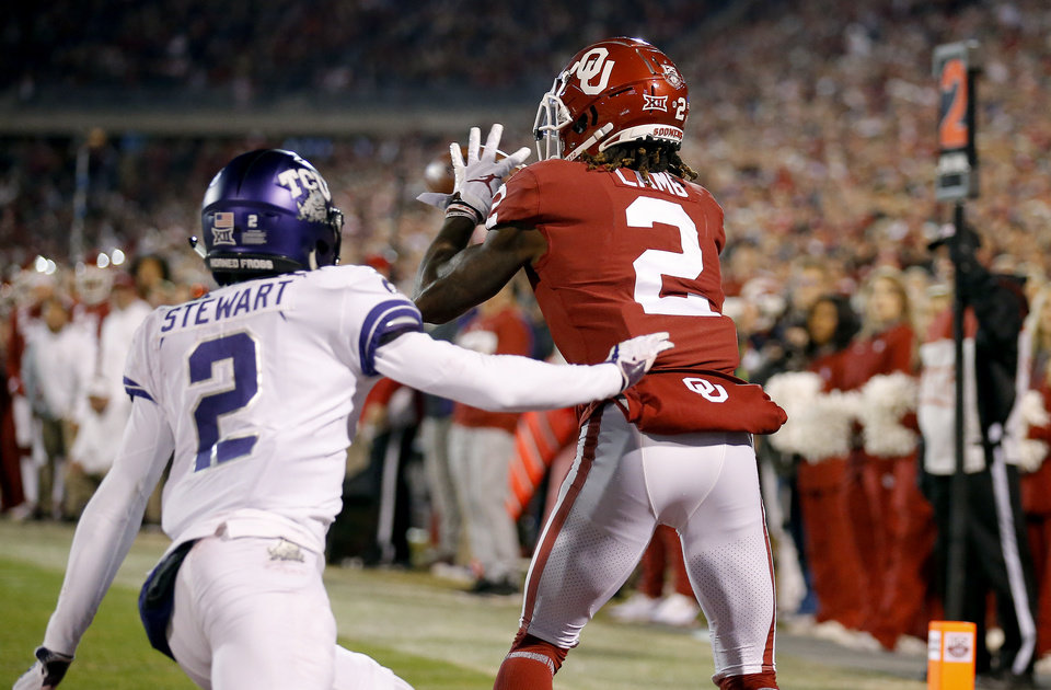 Photo - Oklahoma's CeeDee Lamb (2) catches a touchdown as TCU's Kee'yon Stewart (2) defends in the second quarter during an NCAA football game between the University of Oklahoma Sooners (OU) and the TCU Horned Frogs at Gaylord Family-Oklahoma Memorial Stadium in Norman, Okla., Saturday, Nov. 23, 2019. [Sarah Phipps/The Oklahoman]