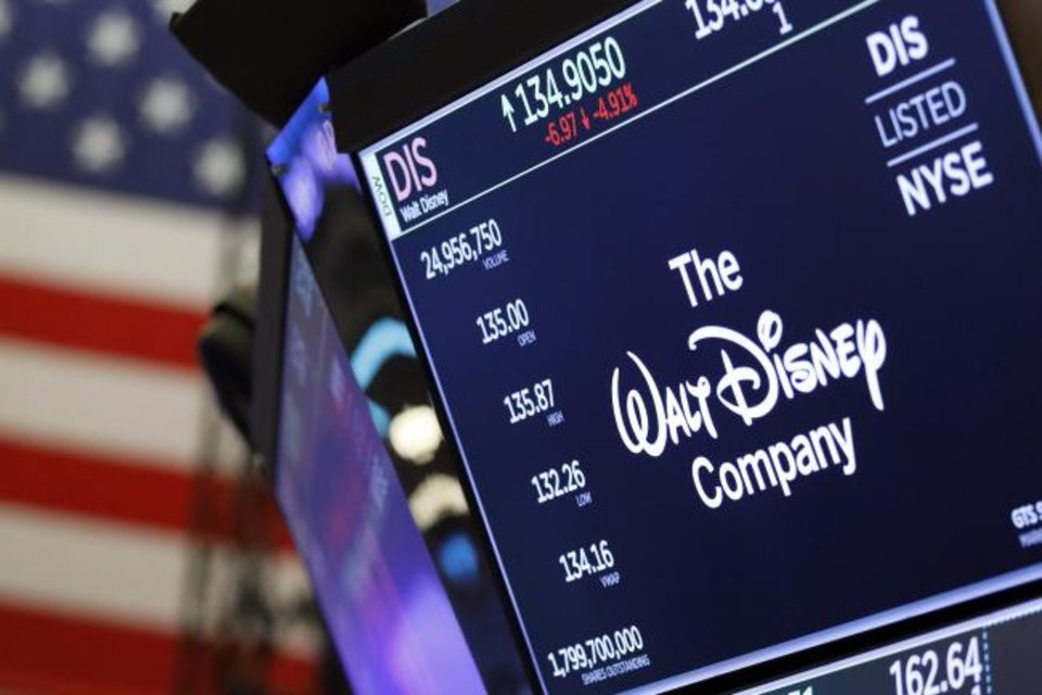 Photo -  The logo for The Walt Disney Company appears above a trading post on the floor of the New York Stock Exchange. [AP PHOTO]