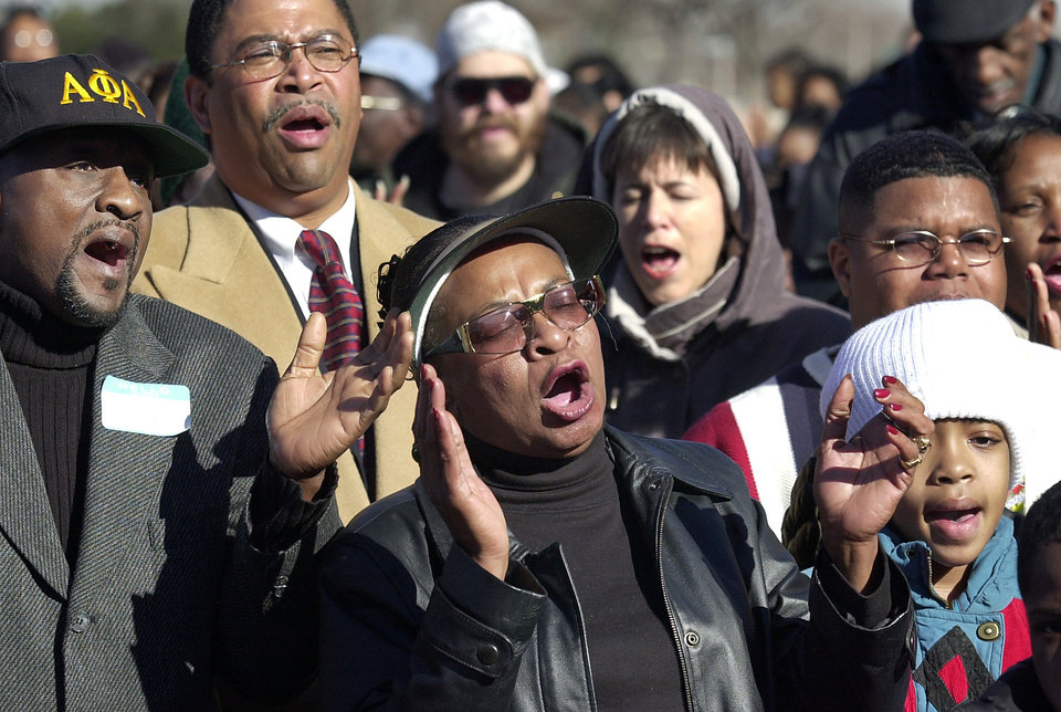 Photo - Marilyn Hildreth, center, sings and claps her hands in time as she joins others in  singing of a Negro spiritual at a ceremony on the front steps of the Oklahoma Historical Society near the state capitol Monday morning.  About 200 people gathered to watch Gov. Frank Keating celebrate Martin Luther King, Jr. Day by ringing the replica of the Liberty Bell on the front lawn of the building.  Hildreth is the daughter of noted Oklahoma civil rights pioneer Clara Luper.  Luper took part in the historic sit-in at Katz Drug Store in downtown Oklahoma City to protest the business' refusal to serve Negro customers.  Staff photo by Jim Beckel.