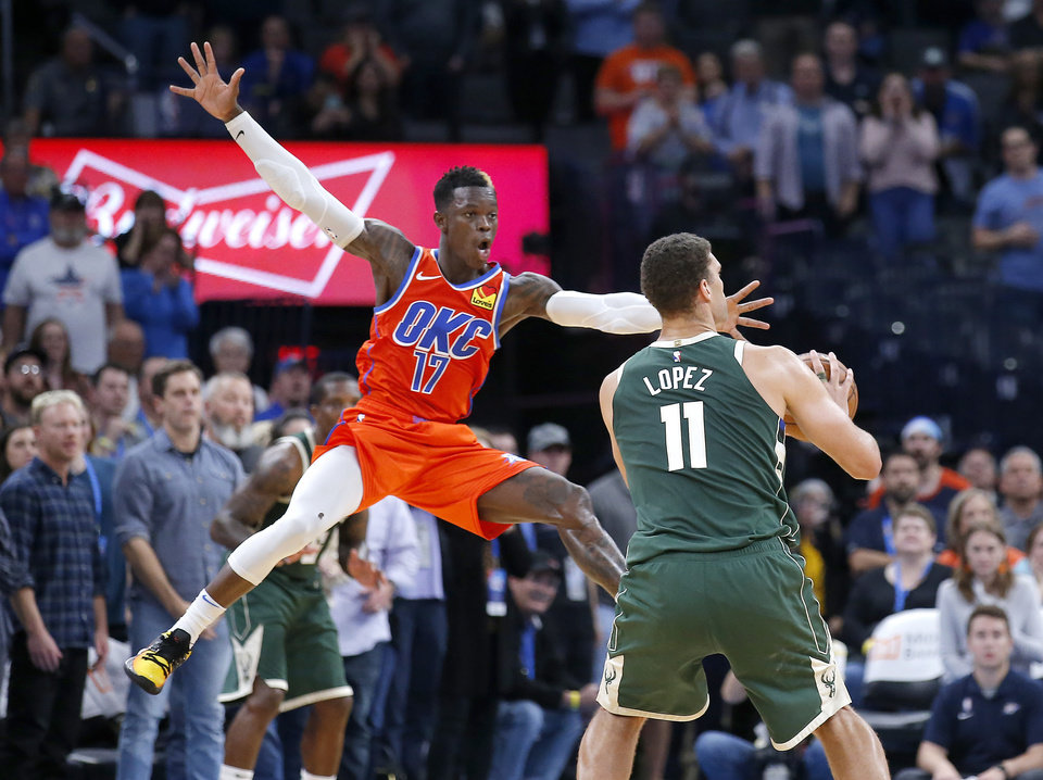 Photo - Milwaukee's Brook Lopez (11) prepares to shoot a 3-point as Oklahoma City's Dennis Schroder (17) defends late in fourth quarter during the NBA game between the Oklahoma City Thunder and the Milwaukee Bucks at Chesapeake Energy Arena,   Sunday, Nov. 10, 2019.  [Sarah Phipps/The Oklahoman]