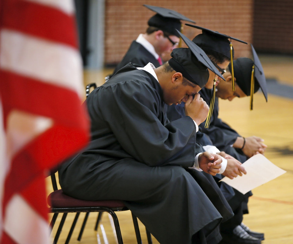 Photo - Julian, front, and other graduates bow their heads during a commencement ceremony for the Oklahoma Youth Academy Charter School at the Central Oklahoma Juvenile Center, a facility for juvenile offenders, in Tecumseh, Okla., Friday, Nov. 17, 2017. The school has multiple graduation ceremonies during the year because of the individual pace at which students earn their high school degrees. Photo by Nate Billings, The Oklahoman