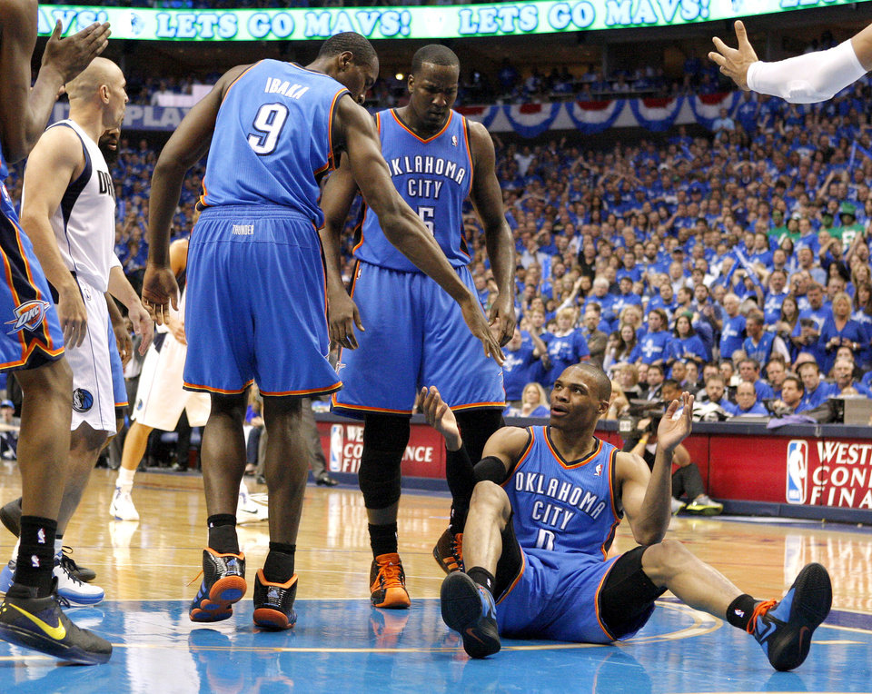Photo - Oklahoma City's Russell Westbrook (0) is helped up by Oklahoma City's Serge Ibaka (9) and Kendrick Perkins (5) during game 1 of the Western Conference Finals in the NBA basketball playoffs between the Dallas Mavericks and the Oklahoma City Thunder at American Airlines Center in Dallas, Tuesday, May 17, 2011. Photo by Bryan Terry, The Oklahoman