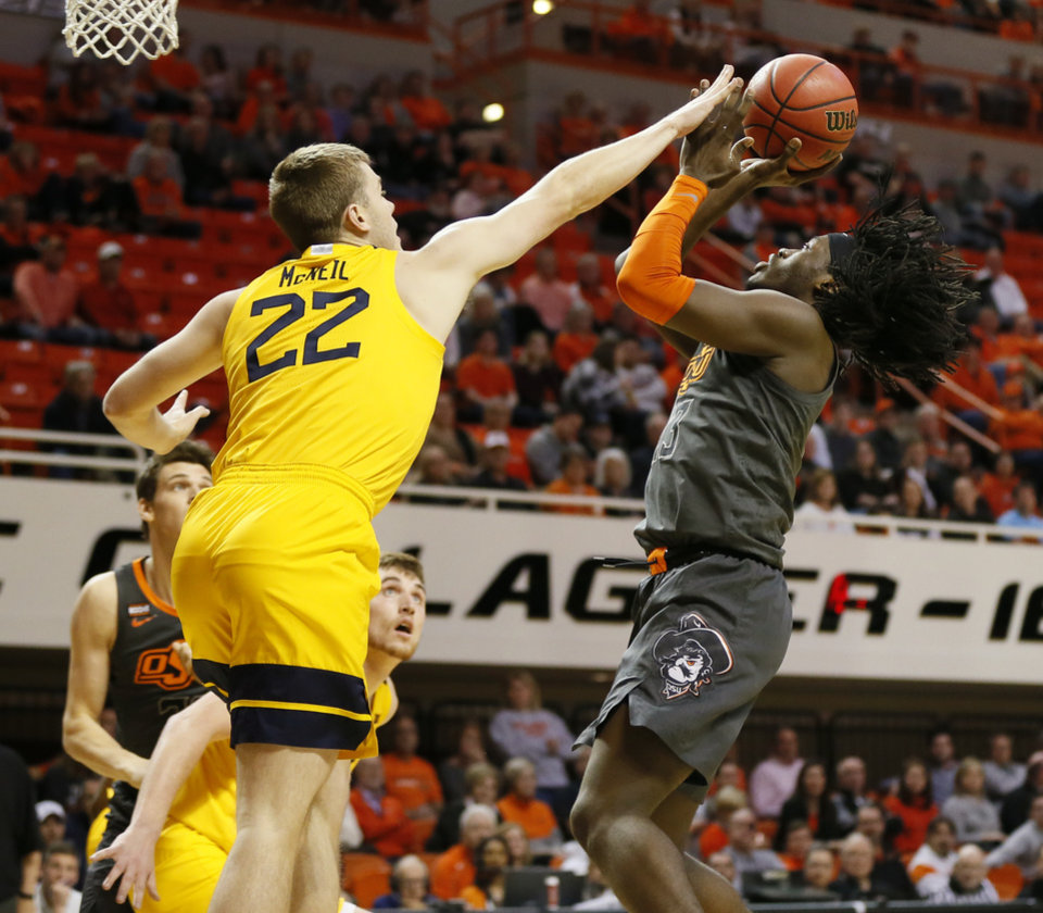 Photo - Oklahoma State's Isaac Likekele (13) shoots against West Virginia's Sean McNeil (22) in the first half during a men's college basketball game between the Oklahoma State Cowboys and West Virginia Mountaineers at Gallagher-Iba Arena in Stillwater, Okla., Monday, Jan. 6, 2020. [Nate Billings/The Oklahoman]
