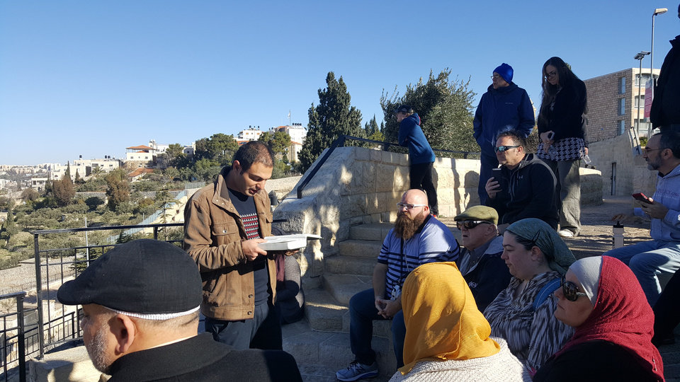 Photo - Mejdi Tours guide Adam Nerk reads a biblical passage during the Oklahoma Religions United group's visit to the Mount of Olives on a tour of Israel in January. [Photo by Carla Hinton, The Oklahoman]