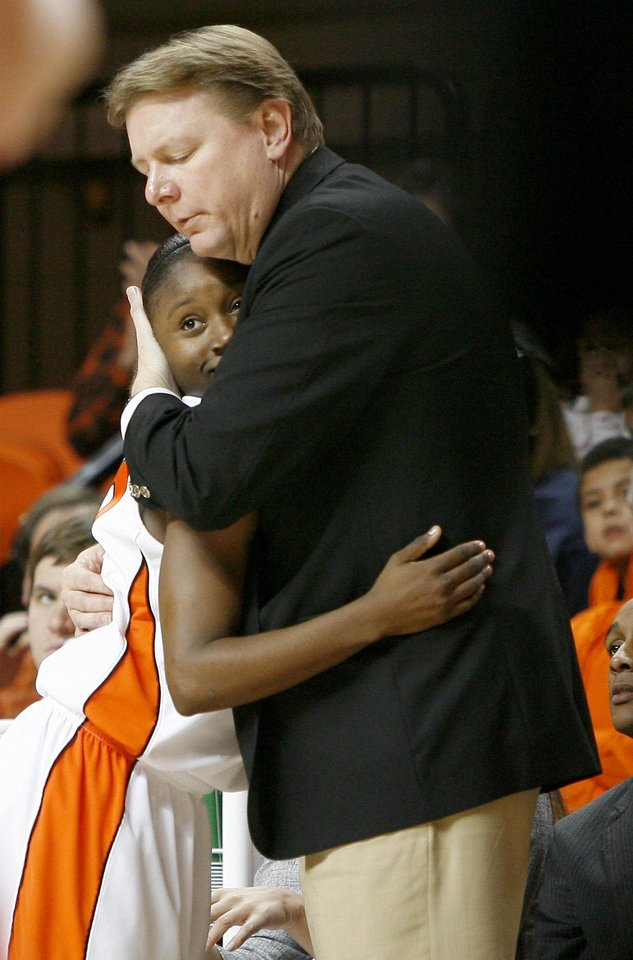 Photo - OSU coach Kurt Budke hugs Andrea Riley as she exits the game during the second half of the NCAA women's college basketball game between Oklahoma State University and Oral Roberts at Gallagher-Iba Arena in Stillwater, Okla., Tuesday, Dec. 22, 2009. Photo by Bryan Terry, The Oklahoman