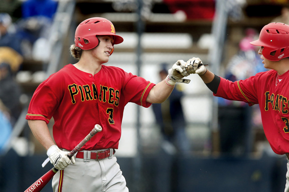 Photo - Dale batter Carson Hunt, left, celebrates with teammate Jono Johnson after Hunt comes across home plate to score one of the Pirates' six runs in the 5th inning during the Class 2A state quarterfinal game at Shawnee High School Thursday, May 9, 2019. Dale advances to the next round of playoffs, defeating Christian Heritage, 11-0.   [Jim Beckel/The Oklahoman]