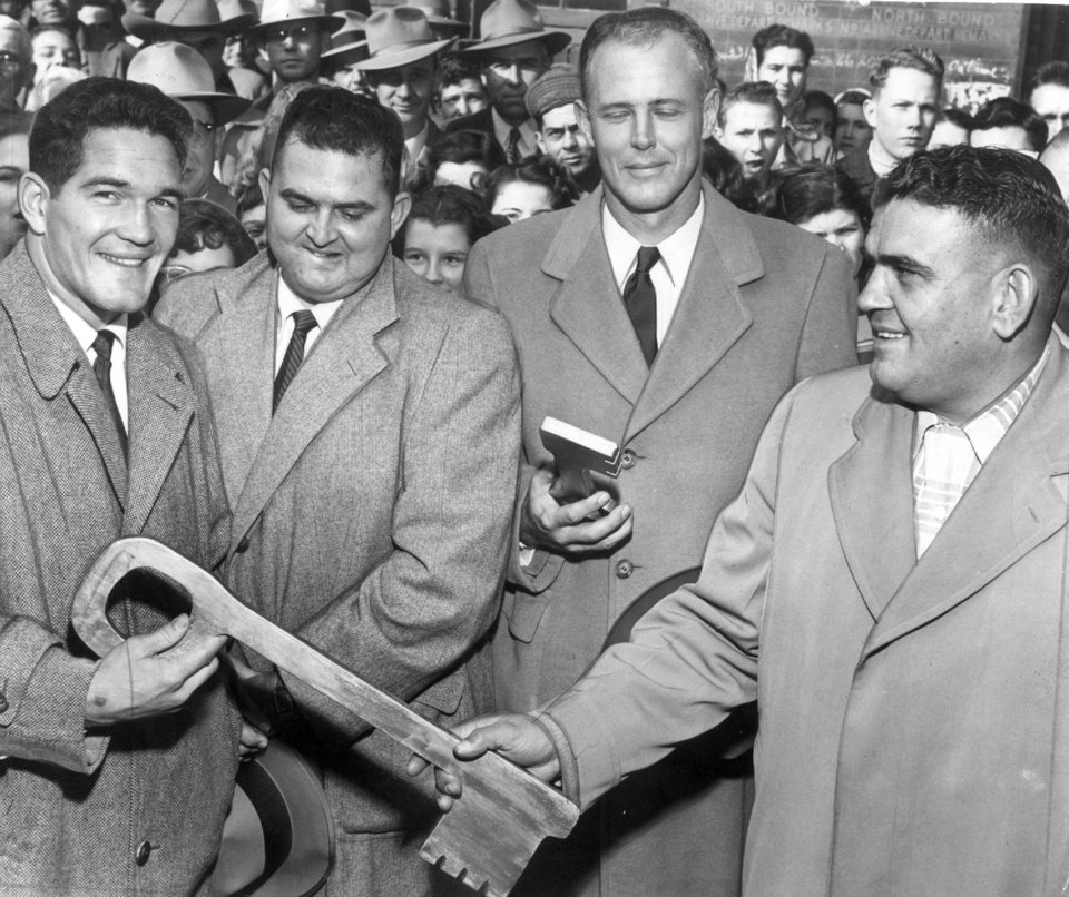 Photo - Cleveland, OK, residents turned out en masse Jan. 20, 1953, to honor their hometown hero, All-American halfback Billy Vessels, left, and his coach, Bud Wilkinson, second from right. Here, Vessels, the Heisman Trophy winner and OU standout, receives the key to the city from City Manager J.D. Cheek, far right, a former Oklahoma A&M player. Also shown is OU assistant coach Dee Andros, between Vessels and Wilkinson. (Oklahoman Archives)
