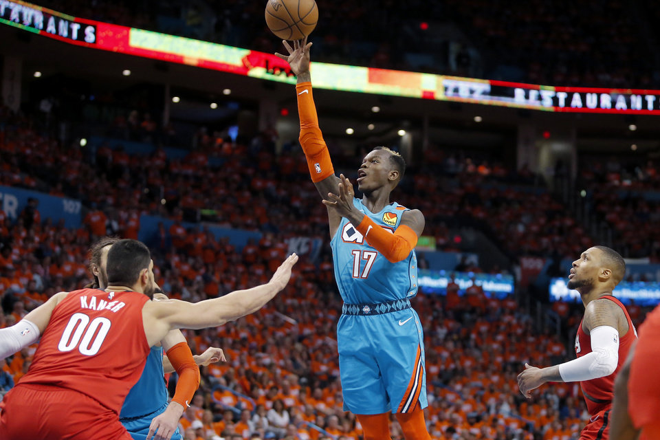 Photo - Oklahoma City's Dennis Schroder (17) shoots a basket from between Enes Kanter (00) and Damian Lillard (0) during Game 3 in the first round of the NBA playoffs between the Portland Trail Blazers and the Oklahoma City Thunder at Chesapeake Energy Arena in Oklahoma City, Friday, April 19, 2019. Oklahoma City won 120-108. Photo by Bryan Terry, The Oklahoman