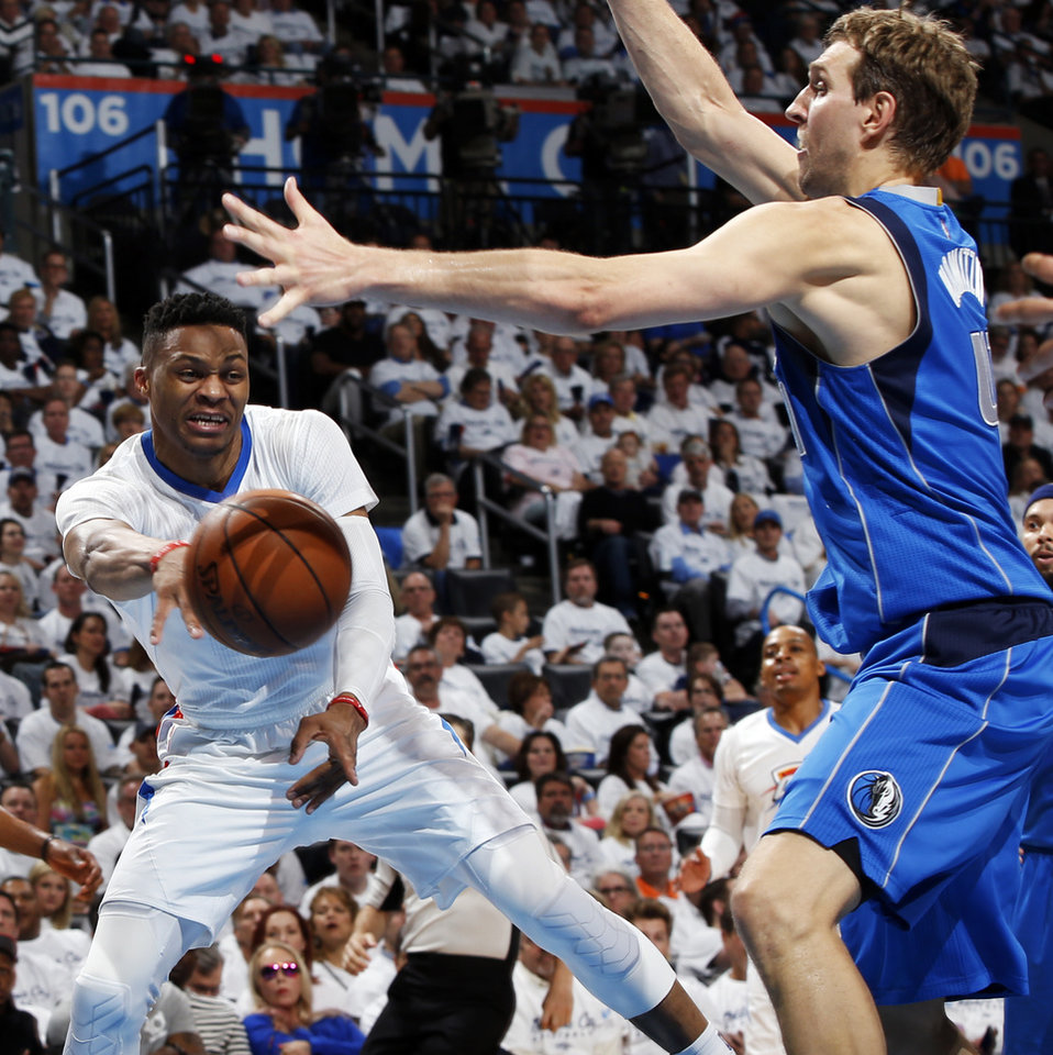 Photo - Oklahoma City's Russell Westbrook (0) passes around Dallas' Dirk Nowitzki (41) during Game 2 of the first round series between the Oklahoma City Thunder and the Dallas Mavericks in the NBA playoffs at Chesapeake Energy Arena in Oklahoma City, Monday, April 18, 2016. Photo by Nate Billings, The Oklahoman