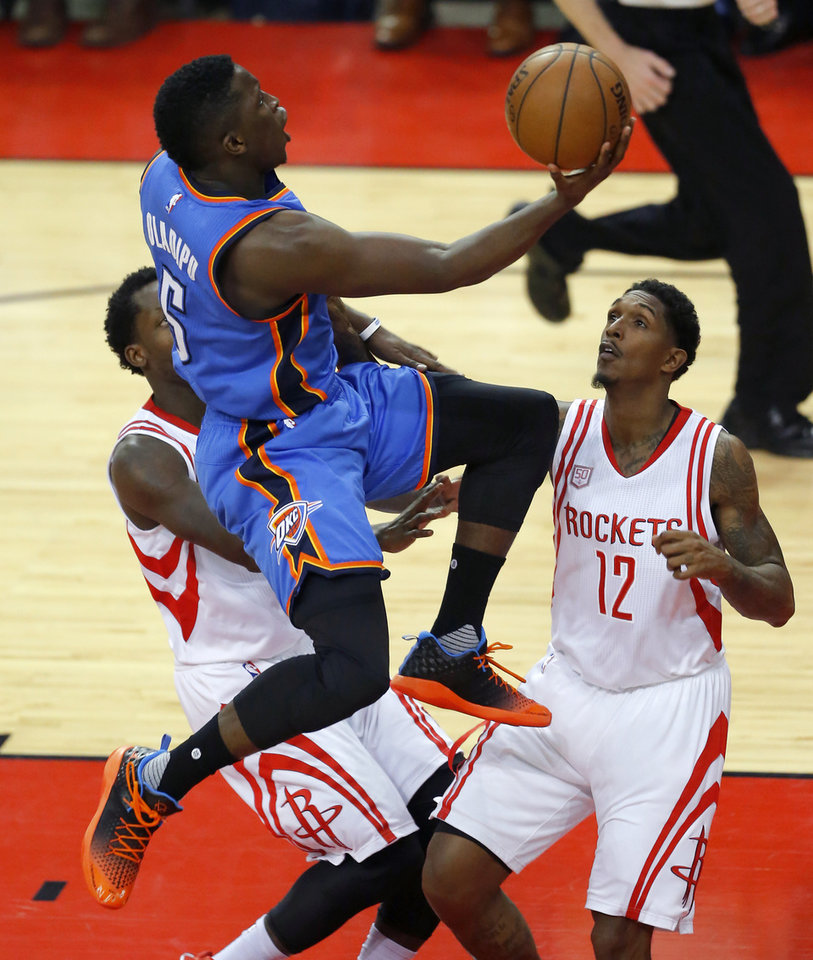 Photo - Oklahoma City's Victor Oladipo (5) goes to the basket past Houston's Lou Williams (12) during Game 2 in the first round of the NBA basketball playoffs between the Oklahoma City Thunder and the Houston Rockets at the Toyota Center in Houston, Texas,  Wednesday, April 19, 2017.  Photo by Sarah Phipps, The Oklahoman