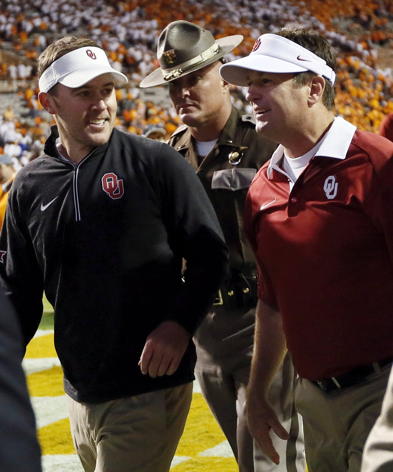 Photo - OU offensive coordinator Lincoln Riley, left, and head coach Bob Stoops talk as they leave the field after the college football game between the Oklahoma Sooners (OU) and the Tennessee Volunteers at Neyland Stadium in Knoxville, Tennessee, Saturday, Sept. 12, 2015. OU won 31-24 in double overtime. Photo by Nate Billings, The Oklahoman