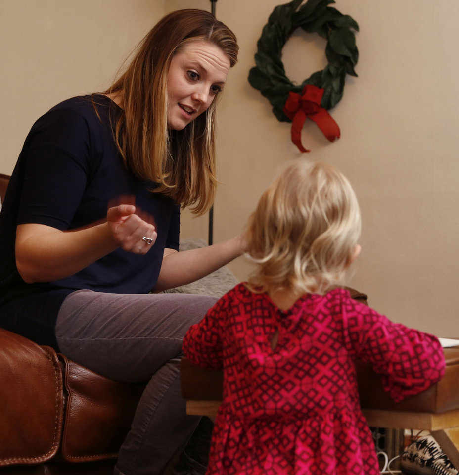 Photo -  Ashley Kehl discusses being a foster parent as she cares for a child at her home in Oklahoma City. [Photo by Paul Hellstern, The Oklahoman]