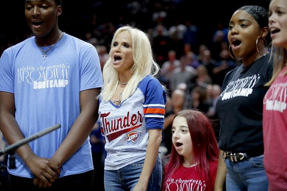 Photo - Kristin Chenoweth, center, sings the national anthem with students from her Broadway Boot Camp before the NBA game between the Oklahoma City Thunder and the L.A. Clippers at the Chesapeake Energy Arena, Tuesday, Oct. 30, 2018. OSU won 38-35. [Photo by Sarah Phipps, The Oklahoman Archives]