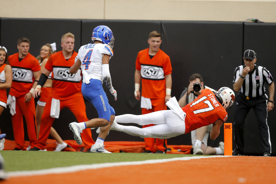 Photo - Oklahoma State's Dillon Stoner (17) leaps past Boise State's DeAndre Pierce (4) for a touchdown during a college football game between the Oklahoma State University Cowboys (OSU) and the Boise State Broncos at Boone Pickens Stadium in Stillwater, Okla., Saturday, Sept. 15, 2018. Oklahoma State won 44-21. Photo by Bryan Terry, The Oklahoman