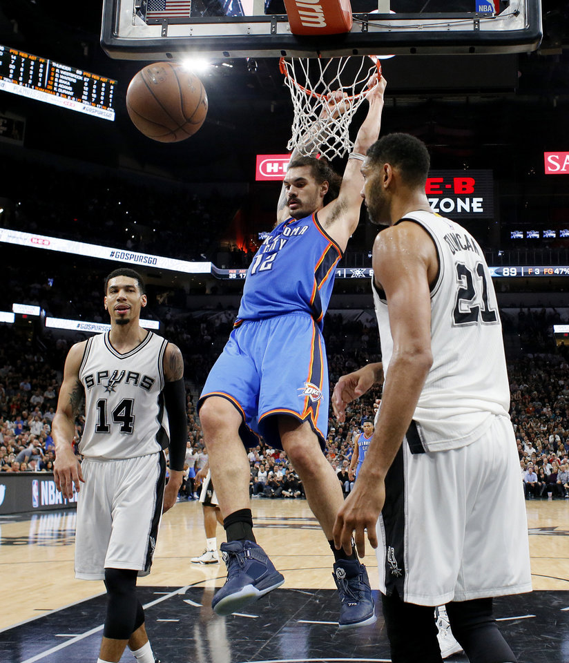Photo - Oklahoma City's Steven Adams (12) hangs on the rim after dunking beside San Antonio's Danny Green (14) and Tim Duncan (21) during Game 2 of the second-round series between the Oklahoma City Thunder and the San Antonio Spurs in the NBA playoffs at the AT&T Center in San Antonio, Monday, May 2, 2016. Oklahoma City won 98-97. Photo by Bryan Terry, The Oklahoman