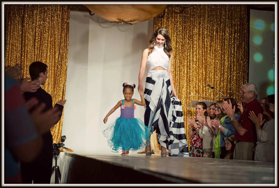 Photo -  Miss Oklahoma Alex Eppler and Miracle Child Jalesa Asimba walk the runway at last year's Linen Runway Show. Photo provided
