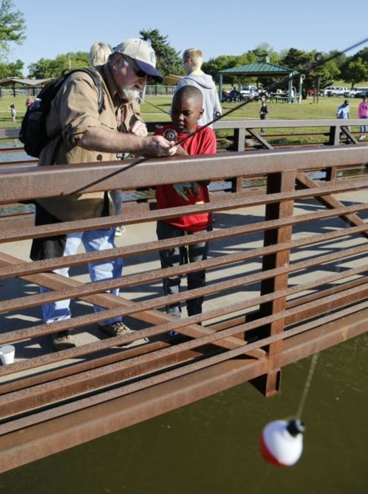 Photo -  Patrick Williams helps Brendan Johnson, then 7, get started during the OKC youth fishing class at Edwards Park Lake in 2017. This year's youth fishing classes begin Saturday. [Oklahoman Archives]
