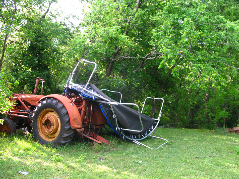 Photo - A trampoline from one of Judy Pendergraft's neighbors is wrapped around a tractor in the Hidden Valley addition in southeast Edmond. Photo by Lillie-Beth Brinkman