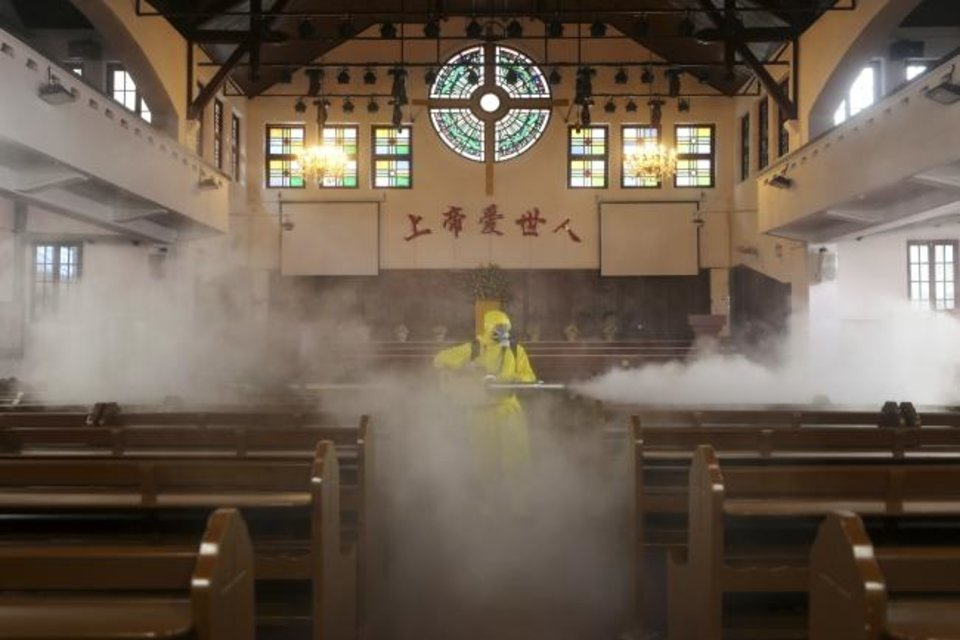 Photo -  A volunteer sprays disinfectant inside a Christian church on March 6 in Wuhan in central China's Hubei Province. [Chinatopix/AP]