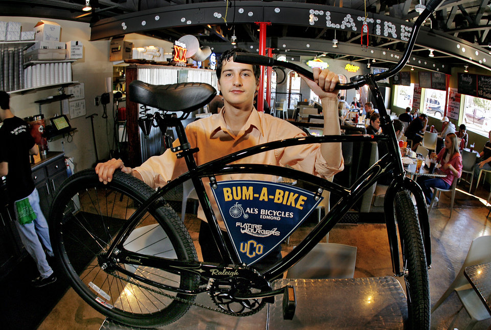 Photo - UCO: Flatire Burger's general manager Jake Kavanaugh poses with a Bum-A-Bike at the restaurant on Thursday, Oct. 18, 2007, in Edmond, Okla. Flatire and the University of Central Oklahoma have teamed up to provide the bikes to students that need a form of transportation around campus and the community.   By CHRIS LANDSBERGER, The Oklahoman  ORG XMIT: KOD