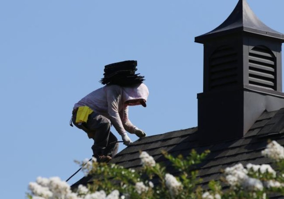 Photo -  A worker carries ridge shingles as Impact Construction Group installs a Fortified roof on Wallace and Karen Mitchell's house in Edmond. [DOUG HOKE/THE OKLAHOMAN]