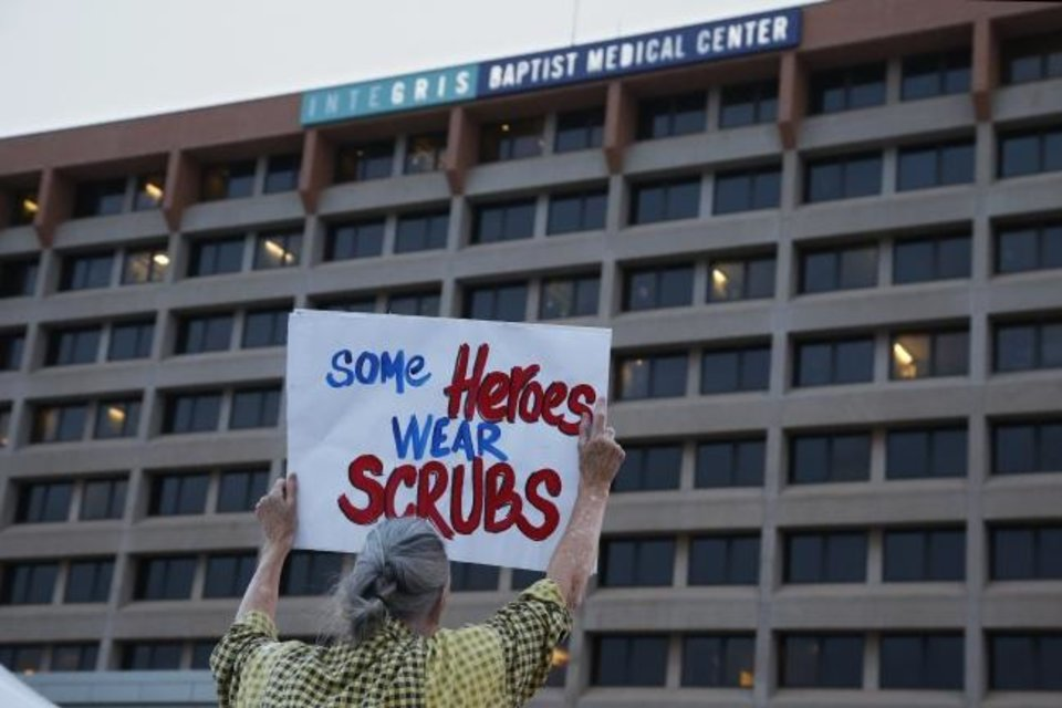 Photo -  A woman holds a sign in the parking lot of Integris Baptist Medical Center during a