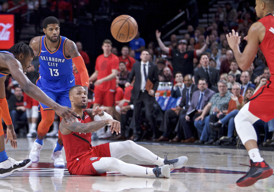 Photo - Portland Trail Blazers guard Damian Lillard, center, passes the ball away from Oklahoma City Thunder forward Jerami Grant, left, and forward Paul George, top, during the second half of an NBA basketball game in Portland, Ore., Friday, Jan. 4, 2019. The Thunder won 111-109. (AP Photo/Craig Mitchelldyer)