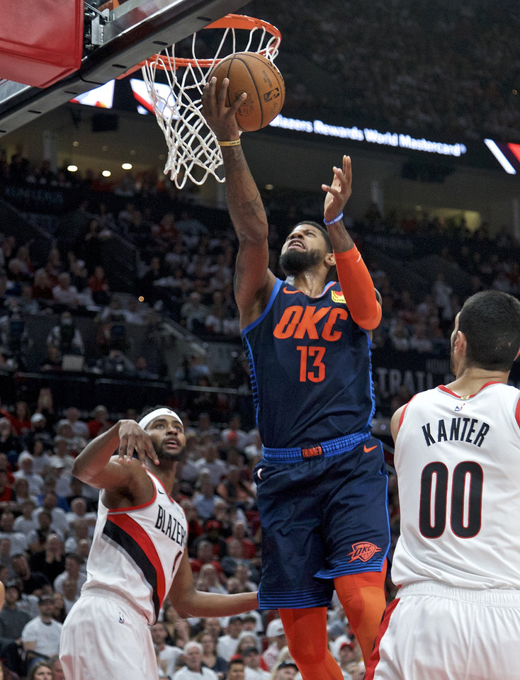 Photo - Oklahoma City Thunder forward Paul George, center, shoots over Portland Trail Blazers forward Maurice Harkless, left, and center Enes Kanter, right, during the first half of Game 5 of an NBA basketball first-round playoff series, Tuesday, April 23, 2019, in Portland, Ore. (AP Photo/Craig Mitchelldyer)