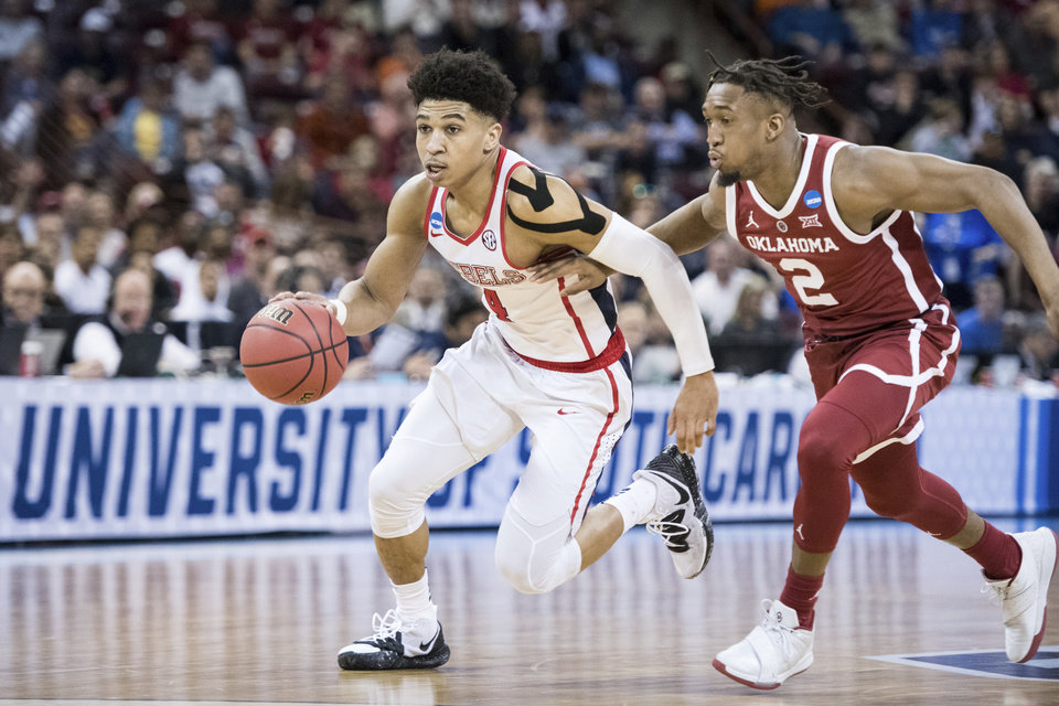 Photo - Mississippi guard Breein Tyree (4) dribbles the ball against Oklahoma guard Aaron Calixte (2) during a first-round game in the NCAA men's college basketball tournament Friday, March 22, 2019, in Columbia, S.C. Oklahoma defeated Mississippi 95-72. (AP Photo/Sean Rayford)