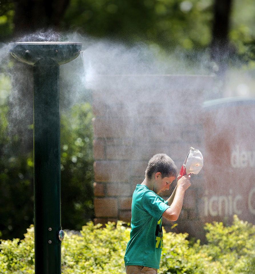 Photo - A boy removes his cap to cool his head beneath one of the water misters at the Oklahoma City Zoo on Wednesday, July 20, 2016.  Photo by Jim Beckel, The Oklahoman