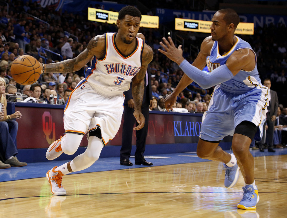 Photo - Oklahoma City's Perry Jones (3) drives the ball past Denver's Arron Afflalo (10) in the second half of an NBA basketball game in Oklahoma City, Saturday, Nov. 1, 2014. (AP Photo/Garett Fisbeck)