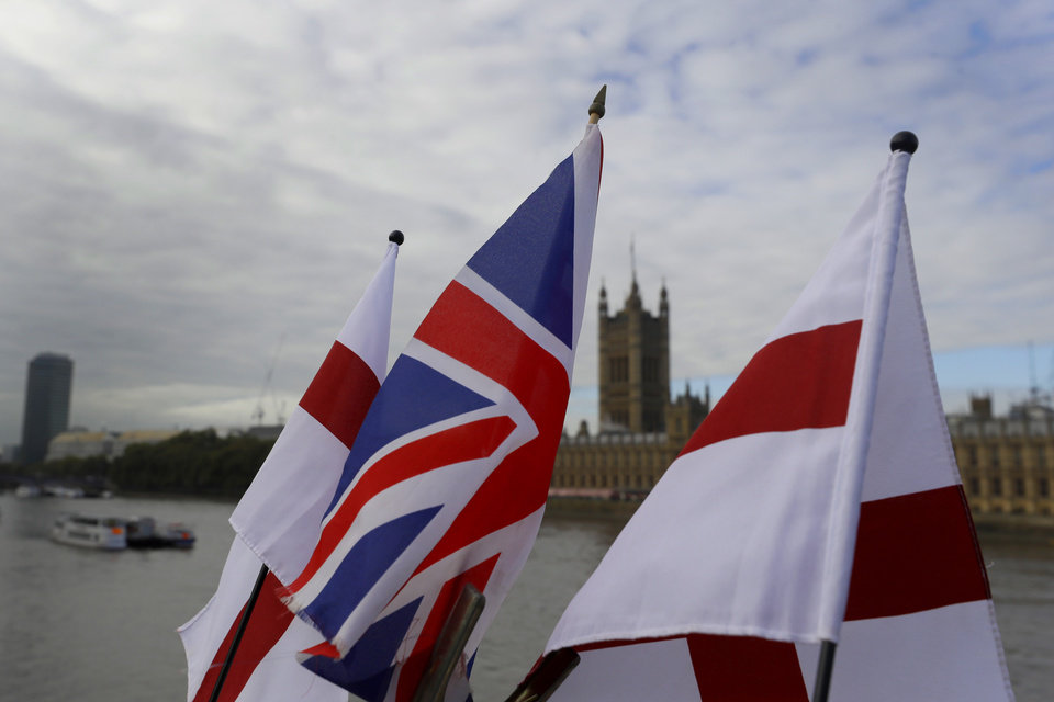 Photo -  English flags and a Union flag fly above a souvenir stand opposite Britain's Parliament on Friday in London. [Kirsty Wigglesworth/The Associated Press]