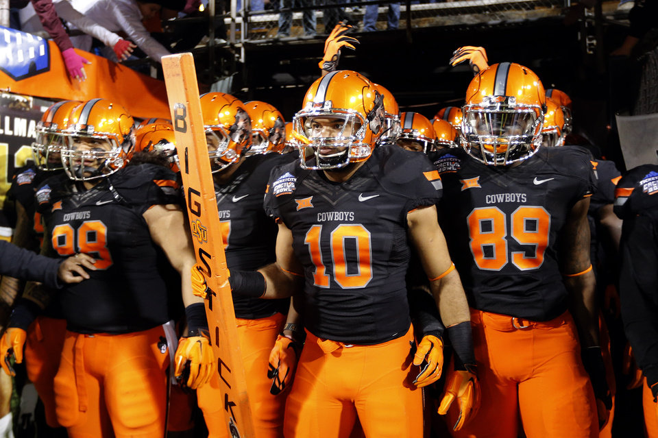 Photo - Oklahoma State's Seth Jacobs (10) leads OSU onto the field before the TicketCity Cactus Bowl college football game between the Oklahoma State Cowboys and the Washington Huskies at the Sun Devil Stadium in Tempe, Ariz., Friday, Jan. 2, 2015. Photo by Sarah Phipps, The Oklahoman
