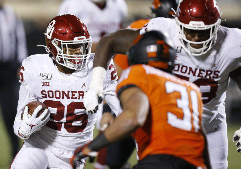 Photo - Oklahoma's Kennedy Brooks (26) carries the ball in the third quarter during the Bedlam college football game between the Oklahoma State Cowboys (OSU) and Oklahoma Sooners (OU) at Boone Pickens Stadium in Stillwater, Okla., Saturday, Nov. 30, 2019. [Nate Billings/The Oklahoman]