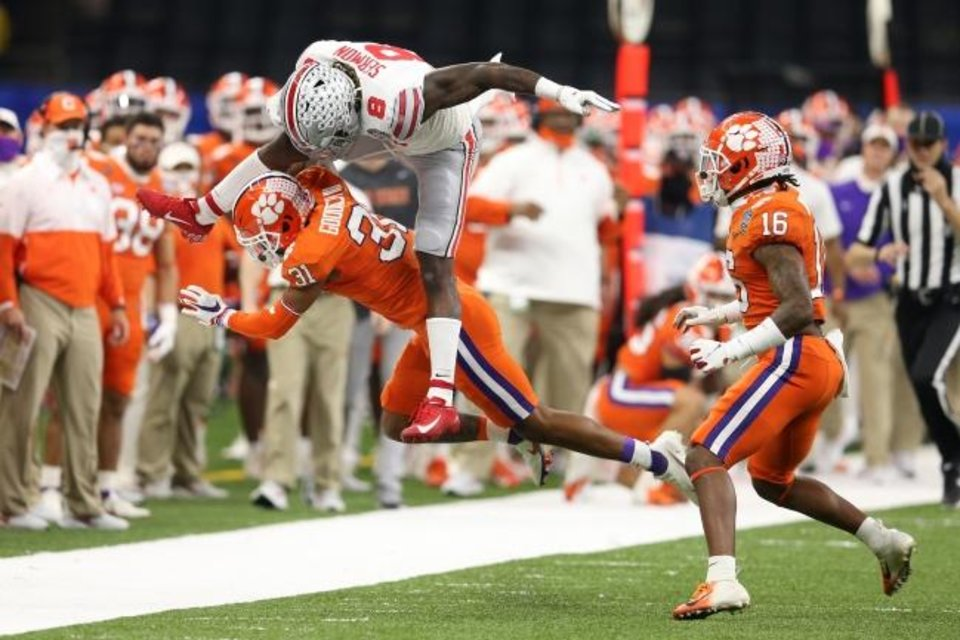 Photo -  Ohio State running back Trey Sermon (8) leaps over Clemson cornerback Mario Goodrich (31) during the first half of the Sugar Bowl on Jan. 1 in New Orleans. [Chuck Cook/USA TODAY Sports]