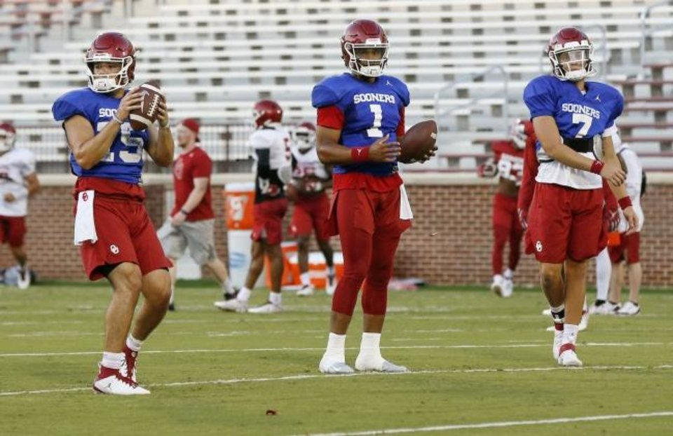 Photo -  From left, Oklahoma quarterbacks Tanner Mordecai (15), Jalen Hurts (1) and Spencer Rattler (7) stand near each other during a passing drill last August in Norman. [Nate Billings/The Oklahoman]