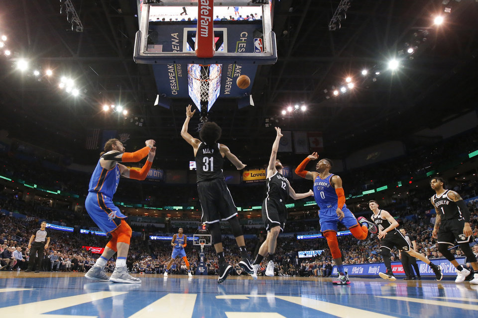 Photo - Oklahoma City's Russell Westbrook (0) throws an  alley-oop pass to Steven Adams (12) as Brooklyn's Jarrett Allen (31) and Joe Harris (12) defend during an NBA basketball game between the Oklahoma City Thunder and the Brooklyn Nets at Chesapeake Energy Arena in Oklahoma City, Wednesday, March 13, 2019. Oklahoma City won 108-96. Photo by Bryan Terry, The Oklahoman