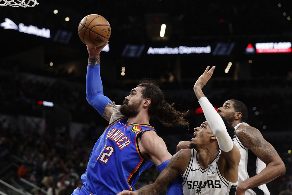 Photo - Oklahoma City Thunder center Steven Adams (12) drives to the basket past San Antonio Spurs guard Dejounte Murray, center, and LaMarcus Aldridge, right, during the first half of an NBA basketball game, in San Antonio, Thursday, Jan. 2, 2020. (AP Photo/Eric Gay)