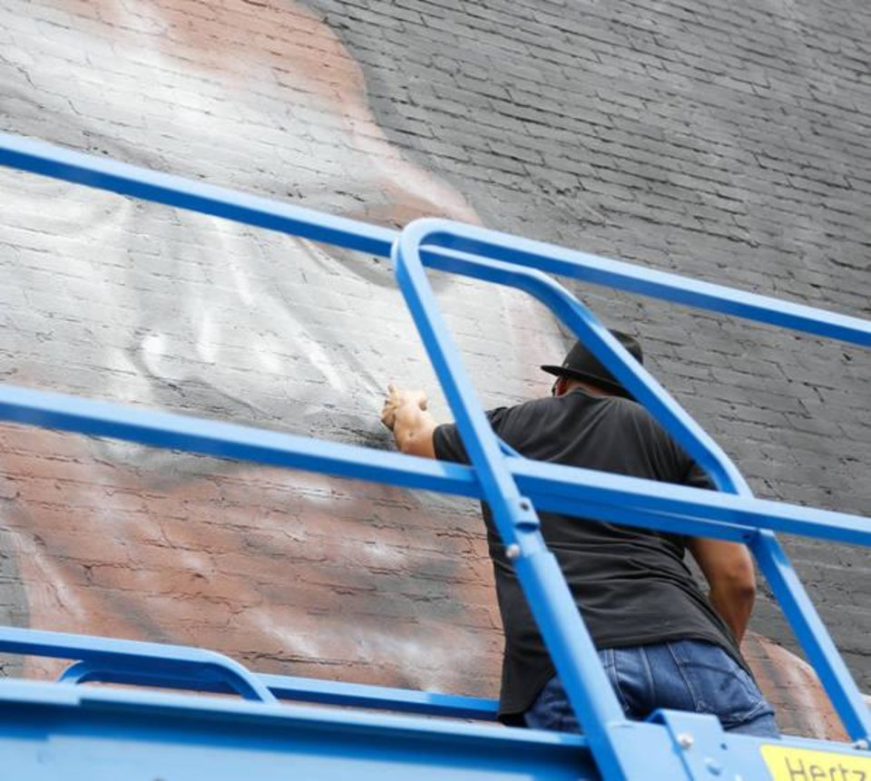 Photo - Graham Hoete, a New Zealander artist living in Australia who is visiting the United States, does detail spray paint work on a mural of Thunder center Steven Adams on a wall of The Paramount in Oklahoma City, Monday, June 13, 2016. Photo by Kurt Steiss, The Oklahoman