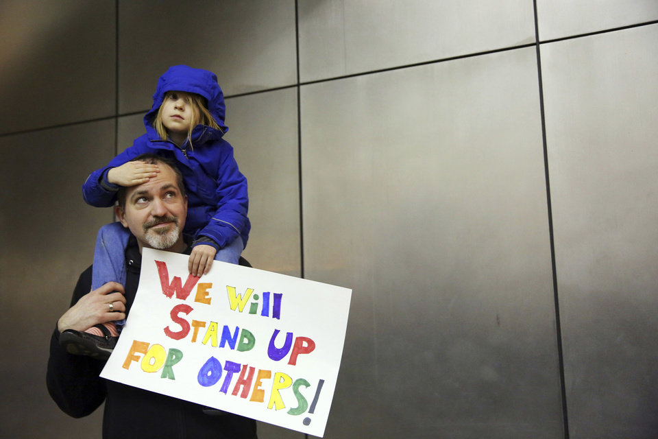 Photo - Matt Sernett holds his daughter Wade, 5, atop his shoulders, as more than 1,000 people gather at Seattle-Tacoma International Airport, to protest President Donald Trump's order that restricts immigration to the U.S., Saturday, Jan. 28, 2017, in Seattle. (Genna Martin/seattlepi.com via AP)